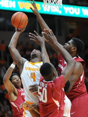 Tennessee forward Armani Moore (4) is swarmed by Arkansas defenders while attempting a layup during the first half at Thompson-Boling Arena on Saturday, Feb. 27, 2016. (ADAM LAU/NEWS SENTINEL)