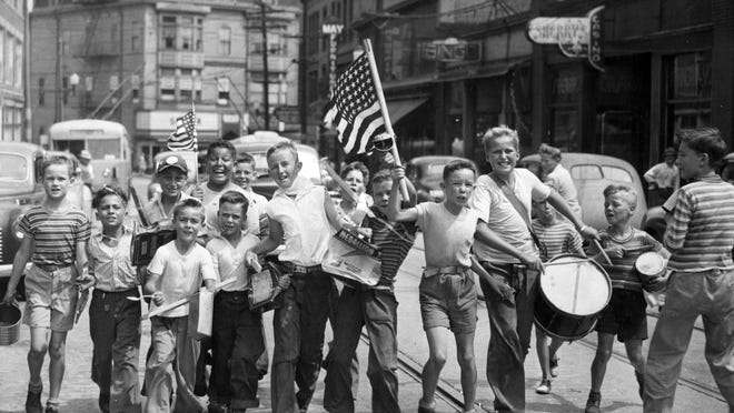 """Pawtucket youths take to the street for an impromptu parade to celebrate the end of World War II in August 1945. From left, David Sutton, Norman Thomas, Alfred Thomas, Donald Freda, Norman Tavares, John Sadlier, Donald O'Gara, Jim Welch, Bob """"Red"""" Luther, Joe McCabe, George """"Buddy"""" Young, Phil Moran, Paul Sutton and Jack """"Cy"""" Welch."""