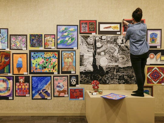 Andrea Ortega, an art teacher at Manitowoc Franklin Elementary School, hangs student work for the MPSD Youth Art Show at the Rahr-West Art Museum Feb. 28.