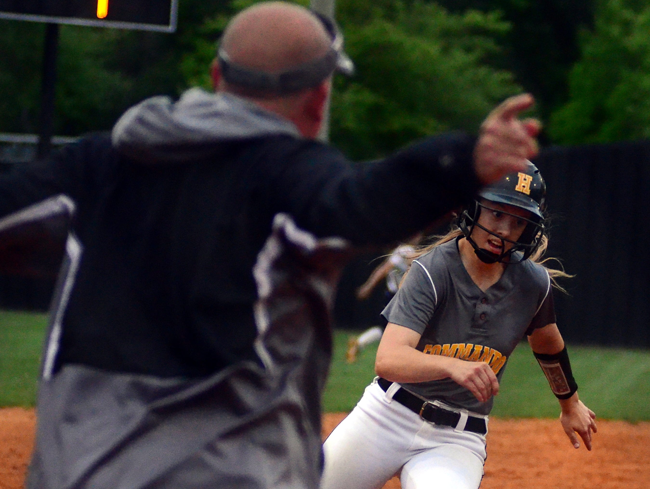 Hendersonville High junior Lexi Revis rounds third base as Lady Commando head coach Jeff Serbin waves her home during third-inning action. Revis scored twice in the Lady Commandos' 5-4 victory.