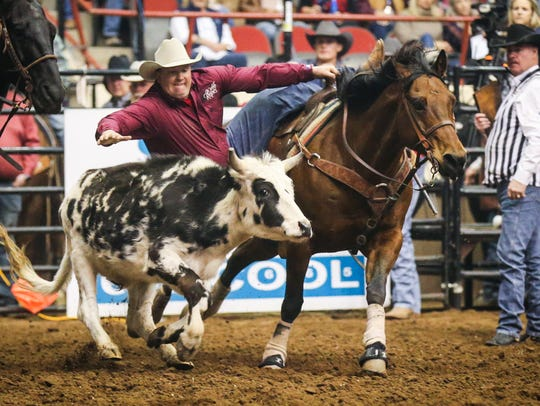 Sam Powers rides out in steer wrestling during the