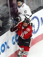 St. Cloud State's Jack Ahcan (red, 12) gets rid of the puck as Nebraska Omaha's David Pope (white, 12) pursues Saturday at Baxter Arena in Omaha, Nebraska.