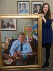 Artist Rose Frantzen of Maquoketa poses with the 3-by-4-foot oil painting of Agriculture Sec. Tom Vilsack that she produced as his official portrait.