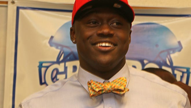 Starkville High School's A. J. Brown smiles as he puts on an Ole Miss hat indicating his choice for college will be to play football at The University of Mississippi during a signing ceremony at Starkville High School on Wednesday, January, 3, 2016.