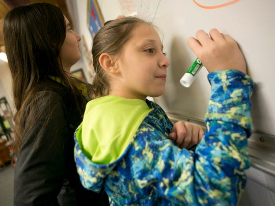 Maryah Ferk, 11, of Wisconsin Rapids, left, and Ashlyn Roffers, 11, of Wisconsin Rapids, right, write on the whiteboard in the Teen Center at the Boys & Girls Club of the Wisconsin Rapids Area at the Pitsch Center, Wednesday, Dec. 2, 2015. The club has started offering a Diploma to Degrees program, designed to help teens to continue their educations after high school.