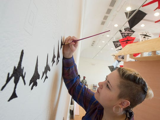 """Autumn Fetterolf, a senior at York College, paints part of a wall mural that will be part of artist installation """"Man Up!"""" by Chris Dacre."""