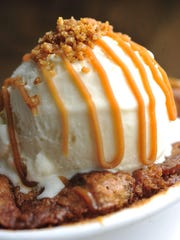 Jack Daniel's-infused Croissant Bread Pudding topped with Jack & Honey gelato, rye whiskey caramel sauce and pecan brittle bits at Goozy Dessert Bar and Cafe.