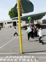 Sherwood students play knockout basketball at a specified station. The balls are also designated colors.