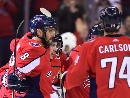 Washington Capitals left wing Alex Ovechkin (8) celebrates the first of his two third-period goals against the Buffalo Sabres during an NHL hockey game in Washington, Saturday, Feb. 24, 2018. Teammates T.J. Oshie, second from left, and John Carlson (74) join in. The Capitals won 5-1. (AP Photo/Susan Walsh)