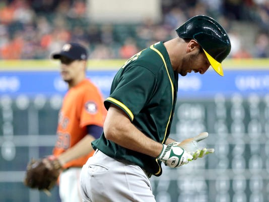 Oakland Athletics' Adam Rosales, right, looks down at his hand after being hit by a pitch thrown by Houston Astros starting pitcher Charlie Morton, left, during the second inning of a baseball game Friday, April 28, 2017, in Houston. (AP Photo/David J. Phillip)