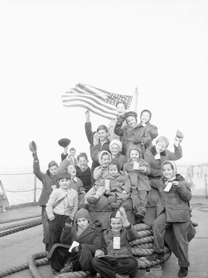 A happy group of Hungarian youngsters needs no prompting to smile for the photographer for this pose aboard the Navy transport Gen. Walker which brought nearly 2,000 Hungarians to New York Feb.15, 1957. They were a part of the largest group of refugees to arrive in the United States through the Government's sea-lift.  After docking, they were transforted to Camp Kilmer, N.J., for processing. (AP Photo/Anthohny Camerano)