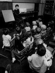 """Inside the """"Secret Room,"""" librarian Barbara Billingsley has the children's full attention as she reads to them."""