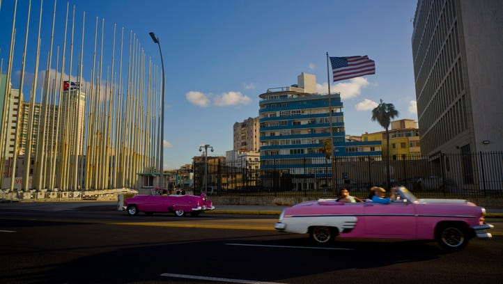 Tourists ride in classic American convertible cars