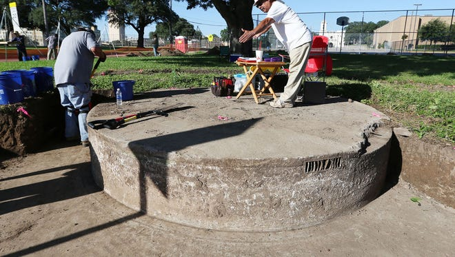 Louis Garcia (right), chairman of the Waco Hispanic Museum, surveys the unearthing of a fountain that once served the Calle Dos neighborhood near present-day Indian Spring Middle School.