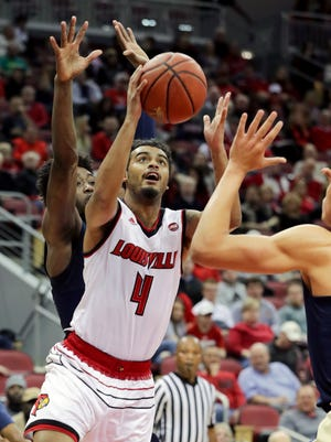 Louisville's Quentin Snider splits two Pittsburgh's defenders for the bucket.