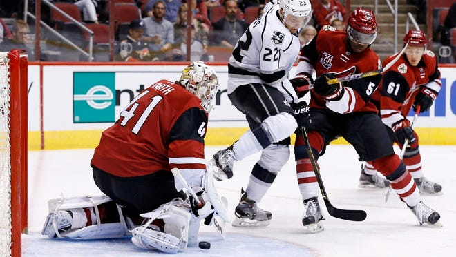 Arizona Coyotes goalie Mike Smith (41) makes a save on a shot by the Los Angeles Kings' Trevor Lewis (22) as the Coyotes' Jalen Smereck (59) and Dysin Mayo (61) defend during the first period of a preseason NHL hockey game Monday, Sept. 26, 2016, in Glendale.