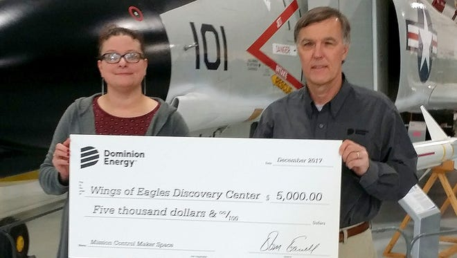 Stan Ossowski, manager of gas transmission operations for Dominion Energy, presents a $5,000 check to Nicole Burt, director of education at the Wings of Eagles Discovery Center.