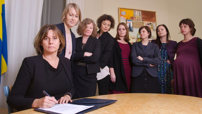 In this handout photo provided by the Swedish Government, Sweden's Deputy Prime Minister Isabella Lovin, left, signs a proposal for the Scandinavian country's new climate law in Stockholm, Friday, Feb. 3, 2017.