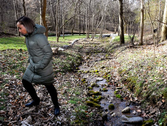 Fawn Weaver walks along a creek on her 313-acre farm