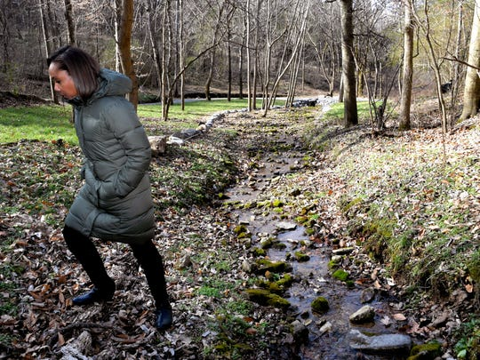 Fawn Weaver walks along a creek on her 313-acre farm in Lynchburg, Tennessee.