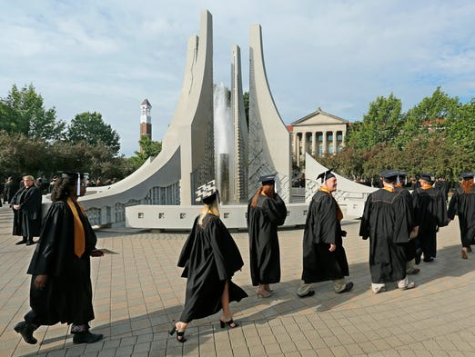Graduates march past the Class of 1939 Water Sculpture as they head to Elliott Hall of Music for summer commencement ceremonies Saturday, August 9, 2014, at Purdue University.