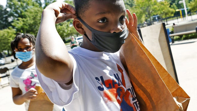 TyShawn Fowler, 8, puts on his face mask. The day camps don't require kids to wear face masks outdoors, but social distancing is adhered to.