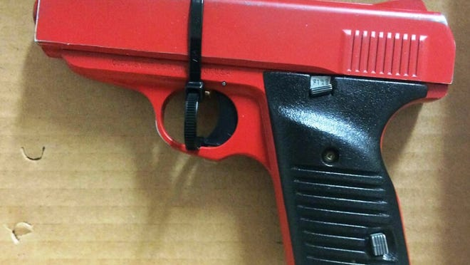This photo provided by the Hamilton County sheriff's office shows a red-painted, .380-caliber handgun police found during the arrest of 23-year-old Orlando Lowery when responding to a call about a man with a gun. The arrest Friday came just four days after legislation was introduced in Ohio to require that lookalike guns be brightly colored or otherwise marked.