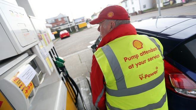 A fuel pump attendant refuels a customer's car at a Shell gas station.