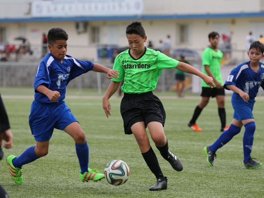 ASC Trust Islanders' Brock Larsen controls the ball facing defensive pressure from Guam Shipyard Wolverines' Yan Ortiz during an opening week U13 division match of the Aloha Maid Minetgot Cup Elite Youth League at the Guam Football Association National Training Center. The Islanders won 6-0.
