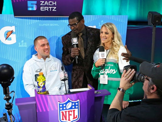 "In this Jan. 29, 2018, photo, Philadelphia Eagles tight end Zach Ertz, from left, is interviewed by Michael Irvin, and Zach's wife Julie Ertz during opening night for the NFL Super Bowl 52 football game at Xcel Energy Center in St. Paul, Minn. Julie and Zach are currently the sporting world's ""It"" couple. Julie is a midfielder for the World Cup-winning U.S. national soccer team, while her husband Zach is a tight end for the Super Bowl-bound Philadelphia Eagles. (AP Photo/Gregory Payan)"