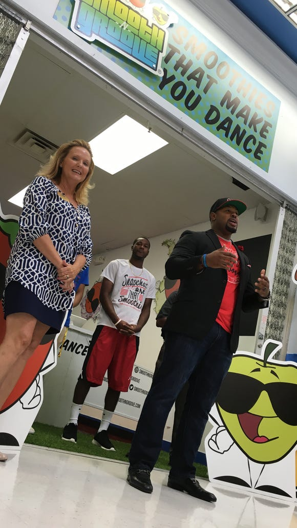 Smooth-N-Groove owner Keon Davis, right, speaks at a ribbon cutting for his new Montgomery location Monday at Walmart on Atlanta Highway.