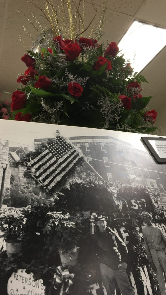 A rose display stands over an undated photo of Rosemont Gardens' float in at Montgomery Veterans Day parade.