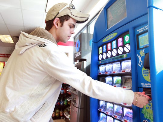 Gabriel Mills of Newport plays a Kentucky lottery machine at a gas station/convenience store in Covington. In the next two years, the state will take $81 million of lottery revenue to cover uses other than education.
