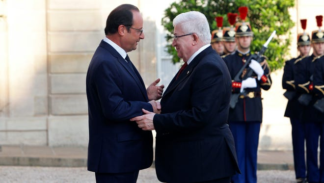 France's President Francois Hollande, left, talks with Iraqi counterpart Fouad Massoum ahead of a conference with U.S. Secretary of State John Kerry at the Elysee Palace, in Paris, Monday.