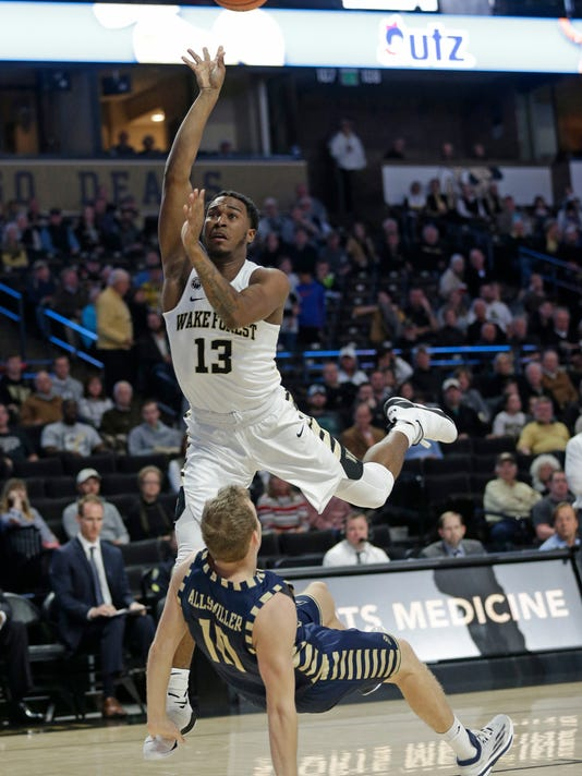 Wake Forest's Bryant Crawford (13) drives into Georgia Southern's Jake Allsmiller (10) while shooting during the first half of an NCAA college basketball game in Winston-Salem, N.C., Friday, Nov. 10, 2017. (AP Photo/Chuck Burton)