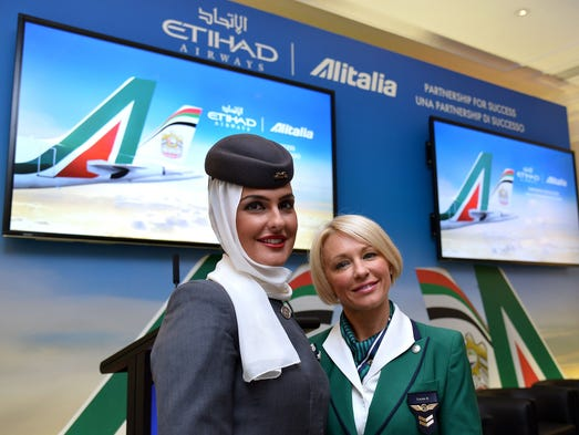 A stewardess of Abu Dhabi airline Etihad Airways and a stewardess of Italian flag carrier Alitalia pose during a press conference in Rome on Aug. 8, 2014.