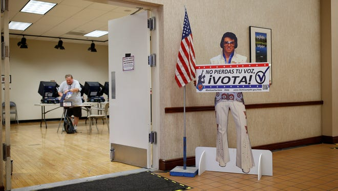 In this May 31, 2016, file photo, a sign with an Elvis impersonator reminds people to vote at an early primary election polling site, in Las Vegas. Seven weeks before Election Day, hundreds of thousands of voters in key battleground states are already requesting early ballots, a sign of rising interest in the 2016 presidential race.