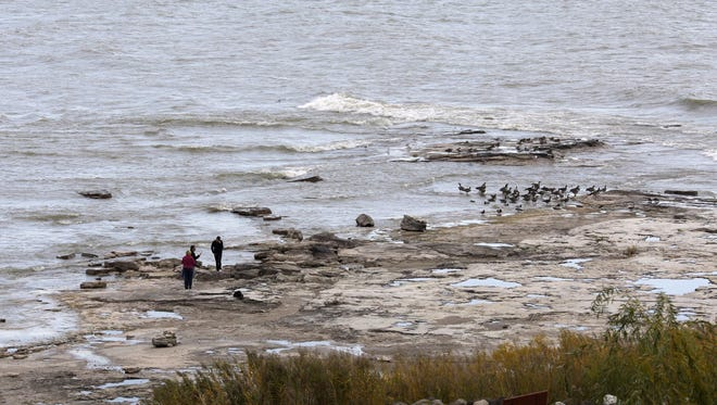 People walk on rock exposed by low water levels in Lake Michigan at Sheboygan's North Point in October 2012.