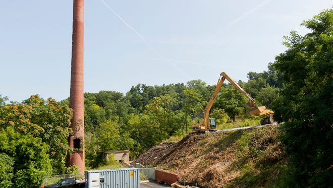 An crew contracted by the City of Ithaca works Thursday to remove the top two feet of contaminated soil from the steep slope between the parking lot of the Gun Hill Apartments and the former Ithaca Gun factory site.