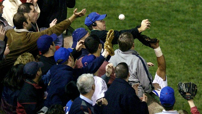 ** FILE ** In this Oct. 14, 2003 file photo, Chicago Cubs left fielder Moises Alou's arm is seen reaching into the stands, at right, unsuccessfully for a foul ball along with a fan identified as Steve Bartman, left, wearing headphones, glasses and Cubs hat, during the eighth inning against the Florida Marlins in Game 6 of the National League Championship Seriesin Chicago. (AP Photo/Morry Gash, File)