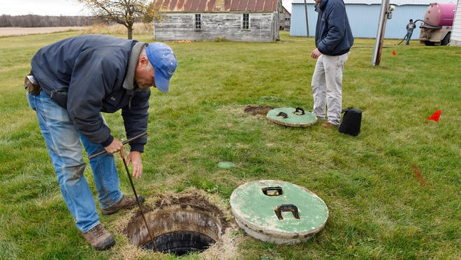 Don Fischer, Watab Inc., checks the bottom of a septic tank for cracks and Ben Pflueger prepares to lower a camera to check baffles during an inspection and certification of a septic system Thursday near Opole. Currently Stearns County requires proof that a septic system is working properly before finalizing the sale of property.