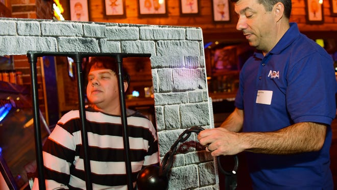 "Lisa Dougherty, left, poses with her ""jailer""  Joe Alfano, Executive director of Muscular Dystrophy Association of Central Pennsylvania, during the Lock Up for MDA event held Thursday, Feb. 25, 2016 at Texas Roadhouse. Community and business leaders had to raise ""bail"" during the  annual fundraiser."