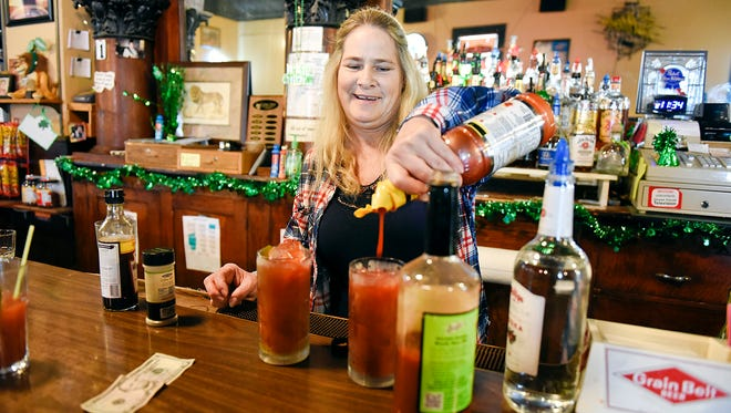 Sandy Brutger, owner of The Lion's Den, makes drinks for customers Friday, March 4, in Avon.