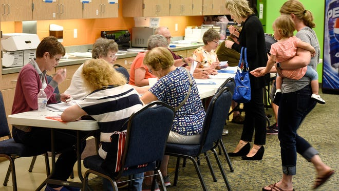 Election officials register new voters and give out ballots Tuesday, May 24, at precincts 5-7 voting at Celebration Lutheran Church in Sartell. Residents of the Sartell-St. Stephen school district are voting on a $105.8 million referendum that would build a new high school and renovate and remodel other district buildings.