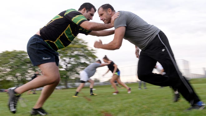 """Zac Bonham, left, and Bryan Woods run through drills on Tuesday, Sept. 27, 2016 during a Crisis Rugby Football Club practice at St. Joe Park in Lansing. """"The team concept, the conditioning, the challenge... It's hard to give up,"""" Woods said. Woods has been with Crisis for two seasons, but has been playing rugby since 1989."""