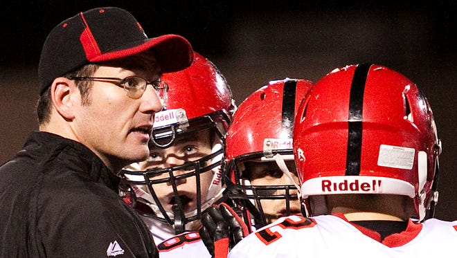 Pewaukee head coach Clay Iverson speaks with his offense during a timeout in the WIAA Division 3 Level 1 playoff game at home against Catholic Memorial on Friday, Oct. 21, 2011.