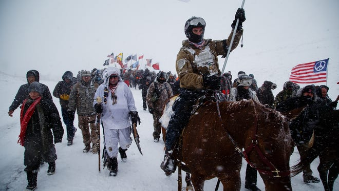 Veteran Cash Jackson leads a veteran's march on the highway 1806 bridge north of the Oceti Sakowin Camp on Monday, Dec. 5, 2016 near Cannon Ball. Officials had been staffing the bridge full time but have said they are going to cut back.
