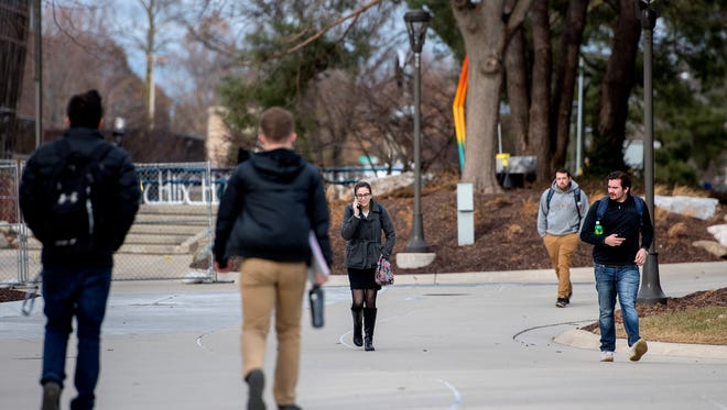 """Pedestrians walk around the Lansing Community College campus on Tuesday, Dec. 5, 2017, in Lansing. Six days earlier police called for an evacuation of the campus after getting a """"credible threat"""" to safety.  A short time later they arrested a man with an AR-15 and ammunition."""