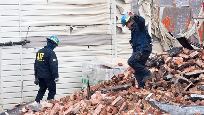 ATF investigators sift through the rubble of the former Weaver Organ and Piano building Sunday morning.