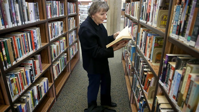 Kitsap Regional Library, Central Branch in Bremerton patron Sharon Newell looks for a book to check out on Friday. She used to be the branch manager at the Port Orchard Library, and had worked at the Central Branch.The library will be opening on Sunday's.